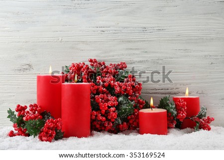 Candles and branch of holly berries in a snow over wooden background, still life - stock photo