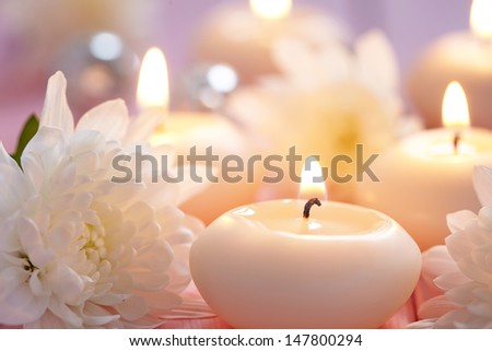 Candles and flowers on wooden table - stock photo