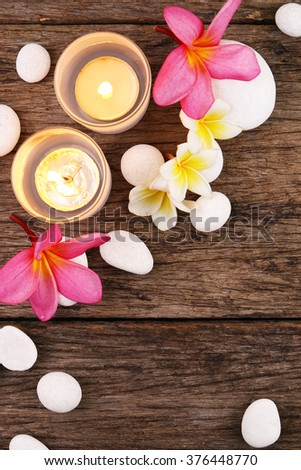 Candles and frangipani flowers on wooden surface
