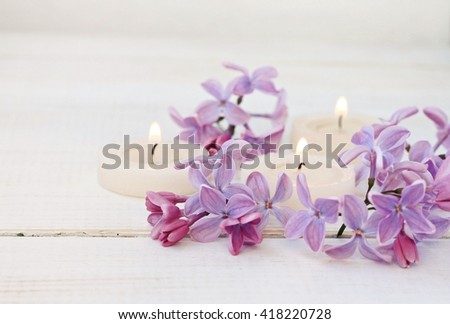 Candles and fresh lilac flowers. Soft light, soft focus. - stock photo