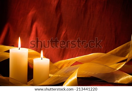 Candles and golden ribbon against a red background for Christmas or the New Year.  - stock photo