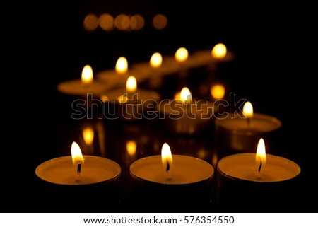 Candles and light reflections on black background.
