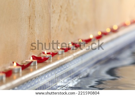 Candles and rose petals in a spa poolside relax and romantic concept  - stock photo