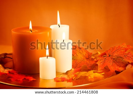 Candles and silk autumn leaves against gold background.  - stock photo