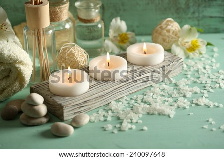 Candles, bottles sea salt and spa stones on wooden background - stock photo
