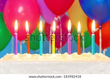 Candles burning on an white iced birthday cake with multicoloured balloons in the background, copy space on the cake to add your own message. - stock photo