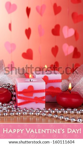 Candles for Valentine Day on wooden table on red background - stock photo