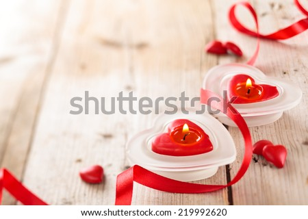 Candles, hearts and ribbon on wooden table.  - stock photo
