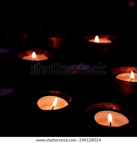 Candles in a church on black background - stock photo