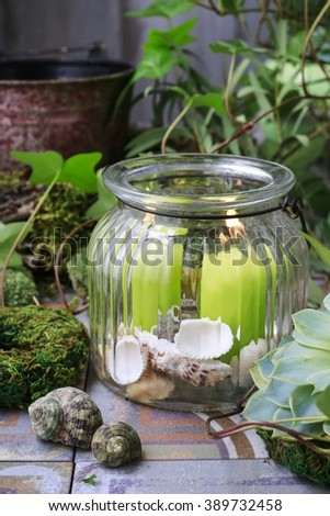 Candles in big glass jar. Garden decoration.