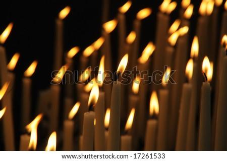 Candles in catholic church on dark background - stock photo