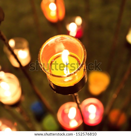 candles in red orange and yellow transparent chandeliers - stock photo