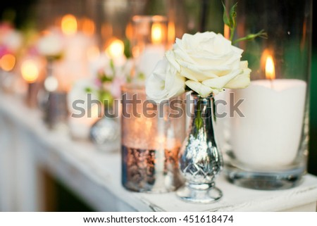 candles in silver glass and small bouquets