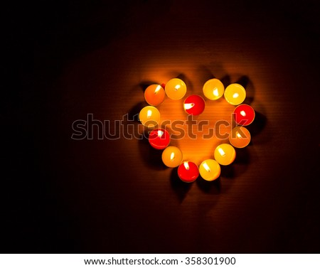 Candles light in heart shape, black background. - stock photo
