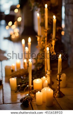 candles on golden candlestick and branches of spruce