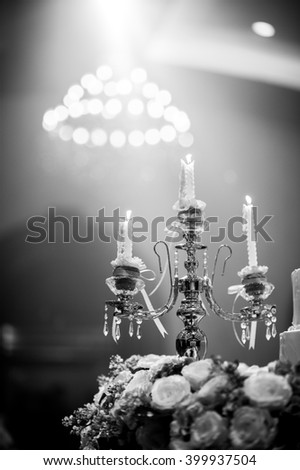 Candles on golden holders at the wedding with bokeh from chandelier background. Decorate of wedding party room in Black and White color - stock photo