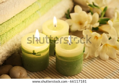 candles towels and freesias on wooden carpet - stock photo