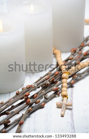 Candles, willow branches and beads on wooden table - stock photo