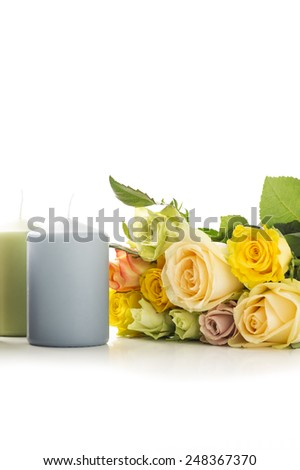 Candles with a bouquet of fresh colorful roses in tribute and remembrance of a departed loved one or as a symbol of love on an anniversary or Valentines Day, vertical on white with copyspace - stock photo