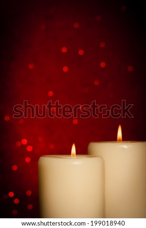 candles with flame on red bokeh background and space for text