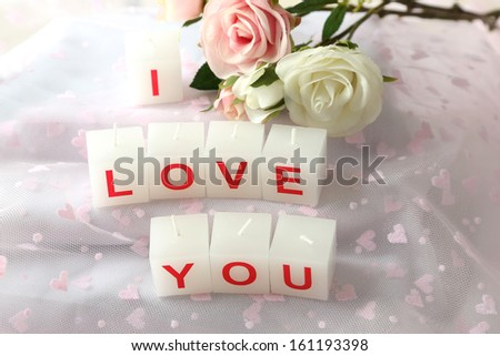 Candles with printed sign I LOVE YOU,on light background - stock photo