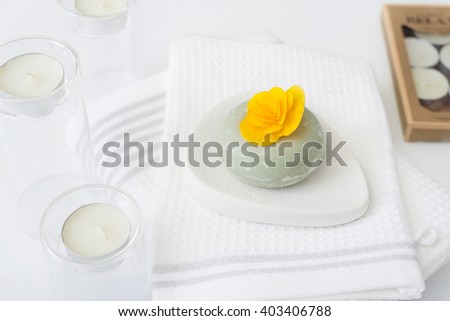 Candles with towels and soap with yellow flower. SPA concept.