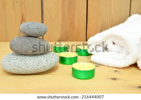 Candles, zen stones and towel on wood