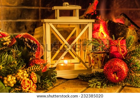 Candlestick against the backdrop of the fireplace and Christmas decorations - stock photo