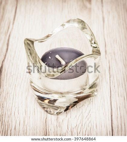 Candlestick of glass with tea lights on the wooden background. Decoration in home. - stock photo