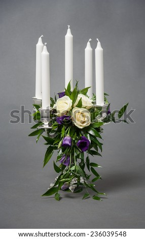 Candlestick with five white candles and roses on grey background - stock photo