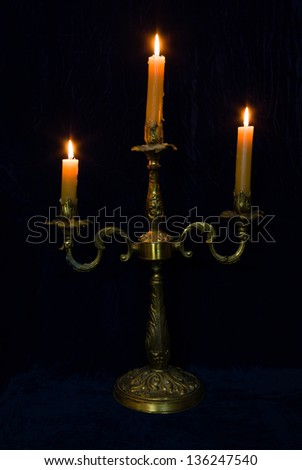 candlestick with three burning candles on background of blue velvet