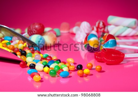 Candy assortment on pink background - stock photo