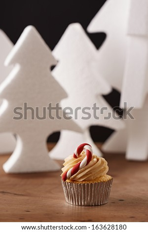 Candy bar cupcake on white Christmas trees background - stock photo