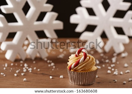 Candy bar cupcake on white snow flakes Christmas background - stock photo