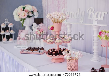 Candy bar. Dessert table for a party. Ombre cake, cupcakes, sweetness.