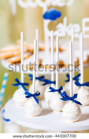Candy bar on baby's christening party with a lot of different candies and beverages. Decorated in blue colors, clouds theme, indoor - stock photo