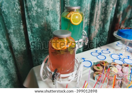 Candy bar on gender reveal party. Lemonade in a large glass jar on a party. Empty glasses for drinks with a straw. - stock photo