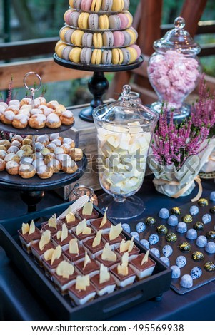 Candy bar with delicious sweets, chocolate candies and other treats in autumn park. Autumn decoration. Natural light