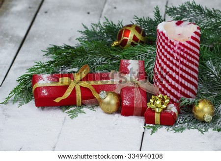 Candy candy Christmas candle, presents and ornaments by green garland surrounded by snow background - stock photo