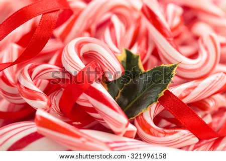 Candy Cane Background. With Holly leaves and ribbon. - stock photo