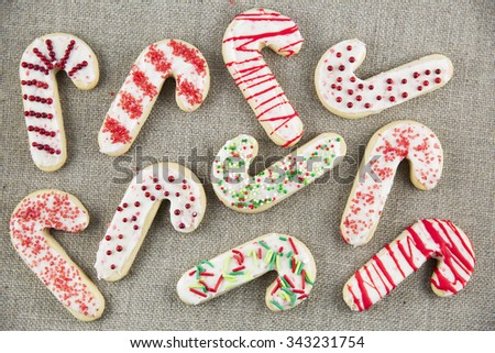 Candy cane shaped sugar cookies with frosting and sprinkles on linen cloth. - stock photo