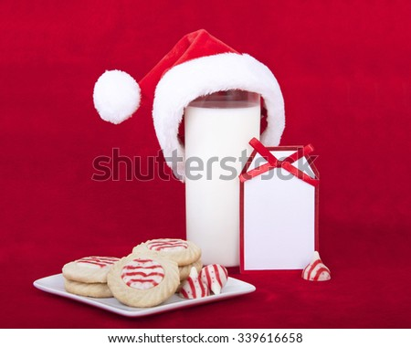 candy cane stripped peppermint flavor sugar cookies on a serving plate with a glass of milk and a miniature santa hat. Note card blank for your message - stock photo