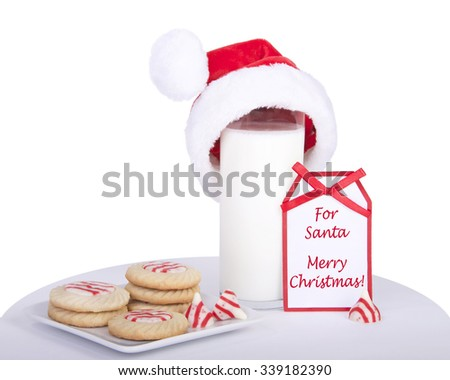 candy cane stripped peppermint flavor sugar cookies on a square plate with a glass of milk wearing a miniature santa hat. Note card next to milk says For Santa Merry Christmas - stock photo