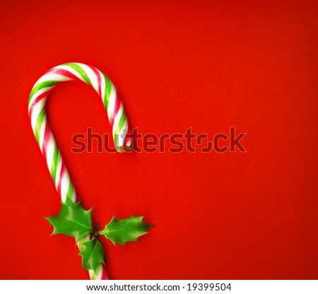 Candy cane with pretty holly leaves on red background, candy cane