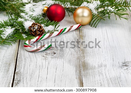 Candy cane with snow covered real Fir tree branches, ornaments, cone and snow on rustic white wooden boards. Christmas season concept. Focus on front part of candy cane.  - stock photo