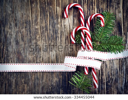 Candy cane with white and red ribbon on wooden background - stock photo