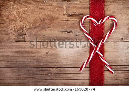Candy canes and ribbon on rustic wooden background - stock photo