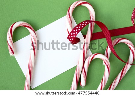 Candy canes and ribbon with copy space on gift tag, all on green background