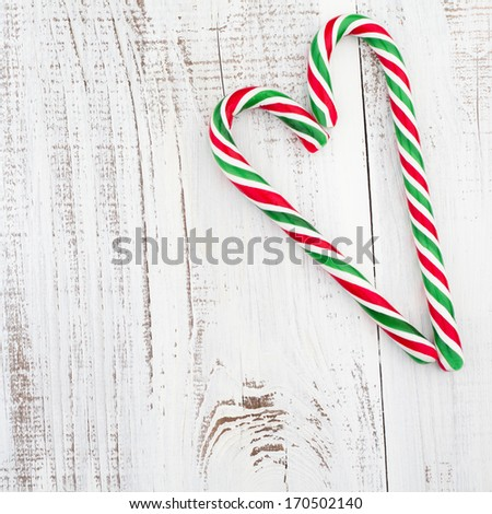 Candy canes as heart on white wooden background.