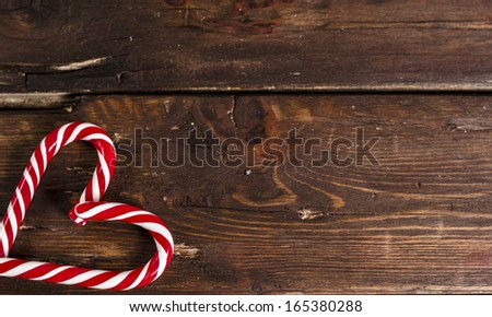 candy canes as heart on wooden table background - stock photo